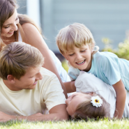 Happy couple laying on lawn with kids