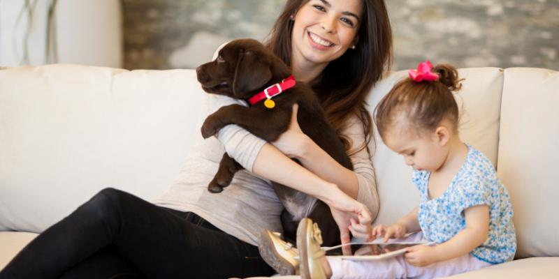 A mom holding a chocolate lab puppy and her toddler playing on an ipad next to her. They are both seated on a tan couch.